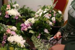Blomsterhandlaren som skapar sammansättning från blommor Arkivbild