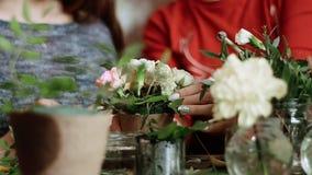Blomsterhandlaren stoppar trevligt klippte blommor i ett litet krukaanseende på tabellen, och instruktören kontrollerar försiktig lager videofilmer