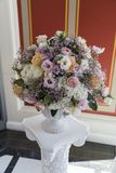 Blomsterrabatt med blommor på sockel i restaurang arkivbilder