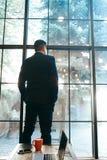 Blomstrande affärsman som står det near fönstret royaltyfri foto