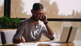 Blomstrande dokument för läsning för försäljningschef och genom att använda bärbara datorn på tabellen och kalla med smartphonen stock video