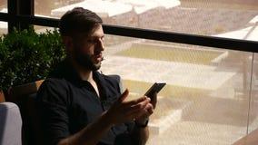 Blomstrande man som använder smartphonen för konversation en maktbank på tabellen lager videofilmer