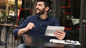 Blomstrande man som segrar i online spel med minnestavlan på kafétabellen lager videofilmer