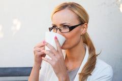 Blon-Haarmädchen in den Gläsern und Klage, die auf der Bank mit Cu sitzt Stockbild