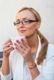 Blon-Haarmädchen in den Gläsern und Klage, die auf der Bank mit Cu sitzt Lizenzfreie Stockfotos