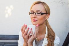 Blon-Haarmädchen in den Gläsern und Klage, die auf der Bank mit Cu sitzt Lizenzfreies Stockfoto