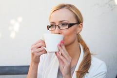 Blon-Haarmädchen in den Gläsern und Klage, die auf der Bank mit Cu sitzt Stockfoto