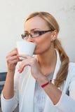 Blon-Haarmädchen in den Gläsern und Klage, die auf der Bank mit Cu sitzt Lizenzfreies Stockbild