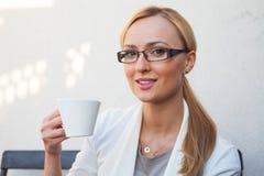 Blon-Haarmädchen in den Gläsern und Klage, die auf der Bank mit Cu sitzt Lizenzfreie Stockbilder