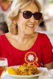 Blond äldre kvinna som ler och sitter på en tabell royaltyfri fotografi
