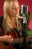 Blond żeńska bawić się gitara akustyczna zdjęcie royalty free