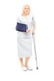 Blond żeński pacjent w todze z łamaną ręką i szczudłem Fotografia Royalty Free
