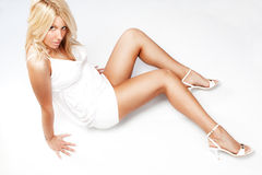 Blond. Good looking blond woman in white dress and high heels sitting on floor Royalty Free Stock Images