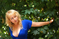 Blond. Beautiful girls stand in green foliage Royalty Free Stock Image