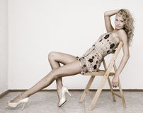 Blond. Young beautiful blonde sitting on wooden chair Royalty Free Stock Photography