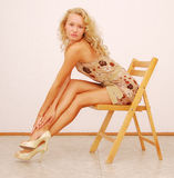 Blond. Young beautiful blonde sitting on wooden chair Stock Image