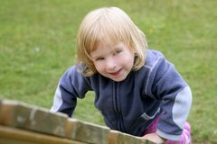 Blond adorable little girl playing playground Royalty Free Stock Images