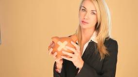 Blond affärskvinna med en piggybank arkivfilmer