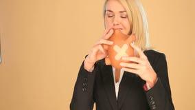 Blond affärskvinna med en piggybank stock video