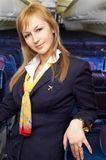Blond air hostess (stewardess). In the empty airliner cabin Stock Photography
