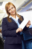 Blond air hostess (stewardess). In the empty airliner cabin Stock Photo