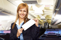 Blond air hostess (stewardess). In the empty airliner cabin Stock Image