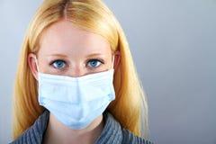 Blond allvarlig kvinna med den kirurgiska maskeringen Royaltyfri Foto