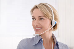 Blond assistant with headphone looking sideways. Royalty Free Stock Photo
