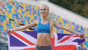 Blond athlete holding flag of Great Britain and rejoicing victory in competition. Stock footage stock video footage