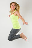 Blond athletic woman jumping in the air Royalty Free Stock Photography