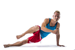 Blond athletic young man exercizing on the floor. Isolated on white background in studio shot Royalty Free Stock Image