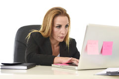 Blond attractive 40s woman in business suit working at laptop co Royalty Free Stock Photos