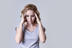 Blond attractive woman on her thirties sad and depressed looking desperate in sorrow. And grief facial expression in female depression emotion concept  on grey Stock Photography