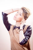 Blond attractive young woman of collected blond hair in brown dress with leather sleeves and collar looking at camera Royalty Free Stock Photography