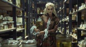 Blond attraktiv kvinna i det retro laboratoriumet Arkivfoto