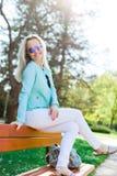 Blond attraktiv kvinna med solexponeringsglas som placerar på bänk royaltyfria bilder
