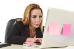 Blond attraktiv 40-talkvinna i affärsdräkten som arbetar på bärbar datordatoren Royaltyfri Bild