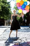 Blond avec des ballons à l'extérieur au soleil image stock