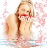 Blond avec les pétales roses et les fleurs rouges et blancs i photographie stock