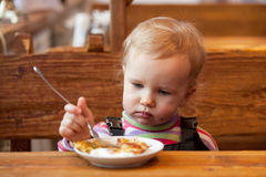 Blond babe eats pancakes at a wooden table Stock Image