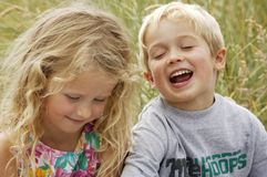 Blond babes. A small blond boy and girl having fun with big smiles and laughter Royalty Free Stock Photography