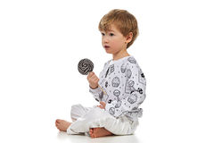 Blond baby boy in pijama with candys Stock Images