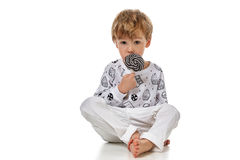 Blond baby boy in pijama with candys Royalty Free Stock Images