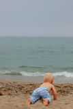 Blond baby crawling to the sea. On the beach on a cloudy day royalty free stock image