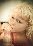 Blond baby girl on the beach. Portrait of a blond baby girl on the beach drinking with a straw Stock Photos