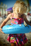 Blond baby girl on the beach. Portrait of a blond baby girl on the beach nice dressed with a swim ring Stock Photography