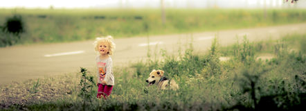 Blond baby girl and dog Royalty Free Stock Photos