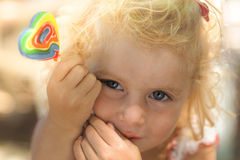 Blond baby girl and lollipop Royalty Free Stock Images