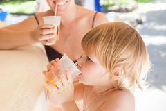 Blond baby girl with mother drink orange juice Royalty Free Stock Image