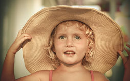 Blond baby girl with summer hat on the beach. Portrait of a blond baby girl on the beach with summer hat Royalty Free Stock Image